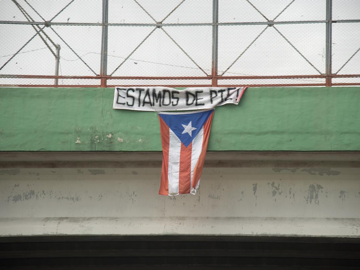 "A flag hangs from a highway overpass that reads ""Estamos de pie,"" in Caguas, Puerto Rico, Oct. 2, 2017. ""Estamos de pie"" translates to ""We are standing,"" which is meant to motivate people to stay strong and overcome the disaster left behind Hurricane Maria. (U.S. Air Force photo by Airman 1st Class Caleb Nunez)"